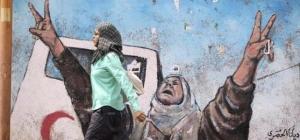 Una mujer pasa junto a un muro reivindicativo en Gaza