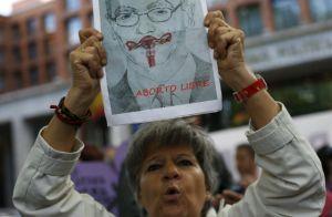 Una mujer levanta un cartel en el que un órgano reproductor femenino tapa la boca de Gallardón. REUTERS