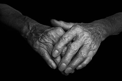Hands of an old woman with wrinkled and wrinkles on dark background.